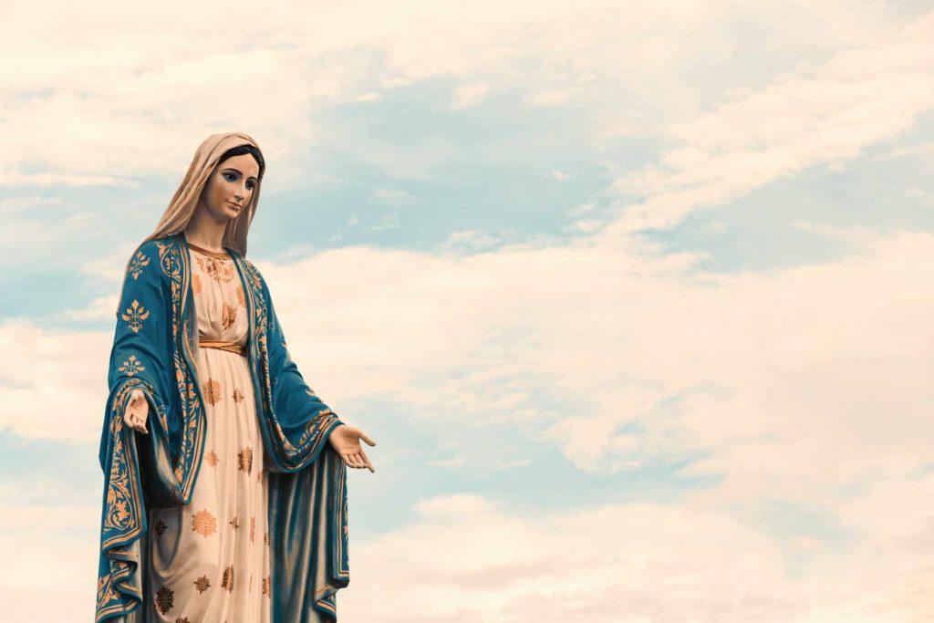 statut de la Vierge Marie avec un ciel bleue et des nuage blanc en fond