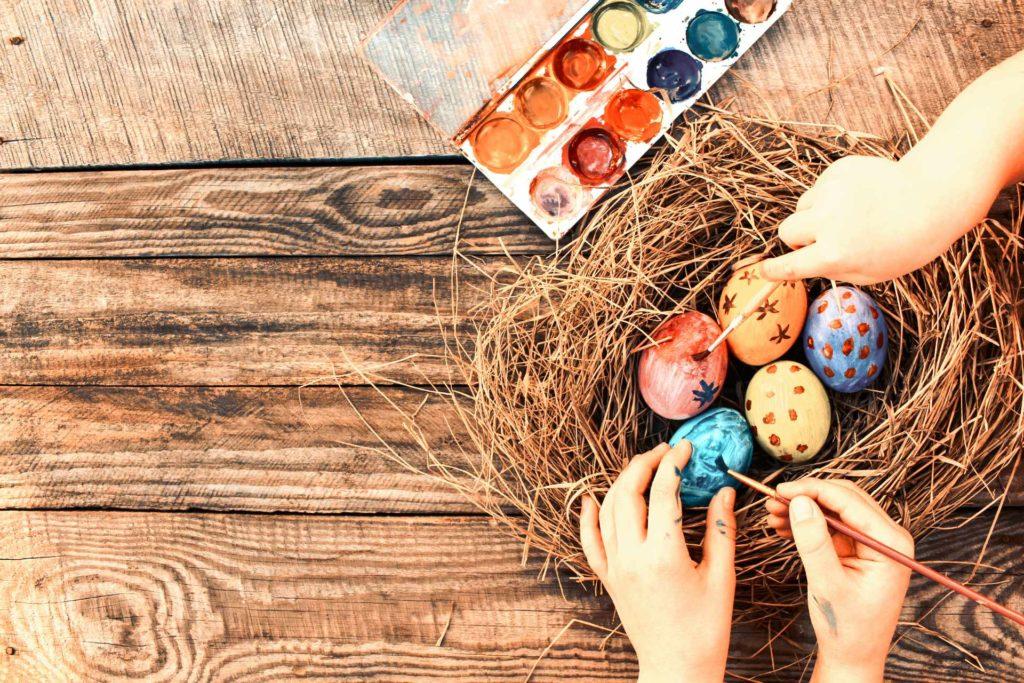 Bricolage d'enfants qui peignent des oeufs de Pâques
