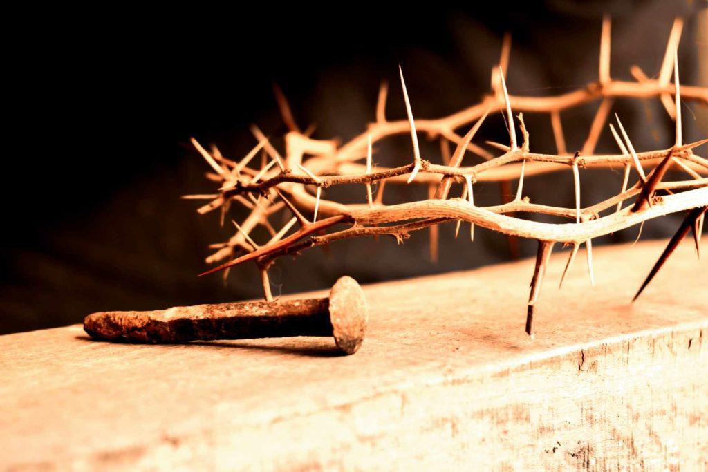 Couronne d'épine du Christ et clou en premier plan le tout posé sur un linteau de bois