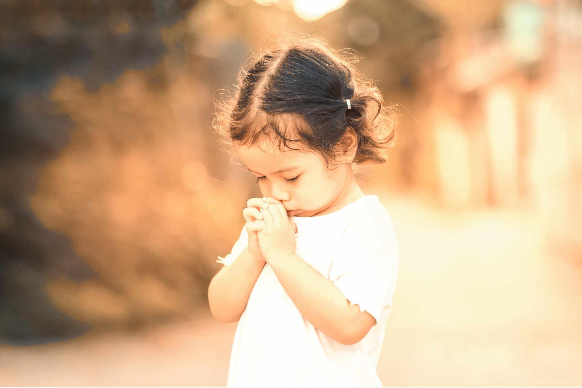 Jeune enfant de 3 ou 4 ans occupé de prier