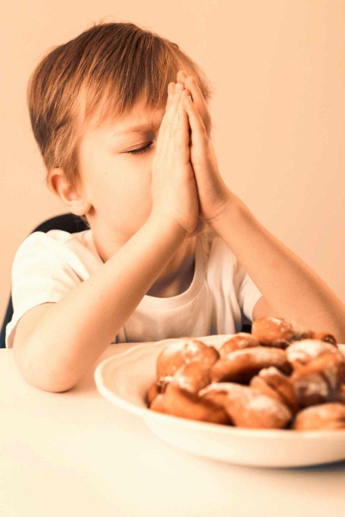 jeune garçon qui prie avant de manger des biscuits
