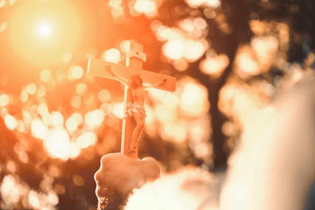 Croix tenue en main avec un soleil qui éclaire la croix