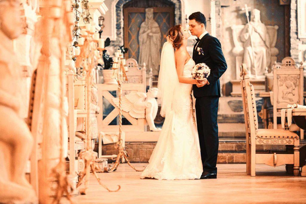 mariés qui se tiennent l'un contre l'autre dans une église