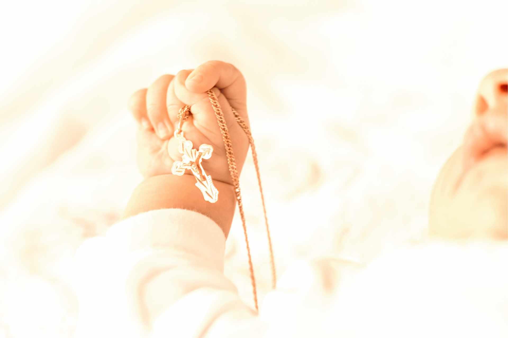 Bébé qui tient une croix dans sa main