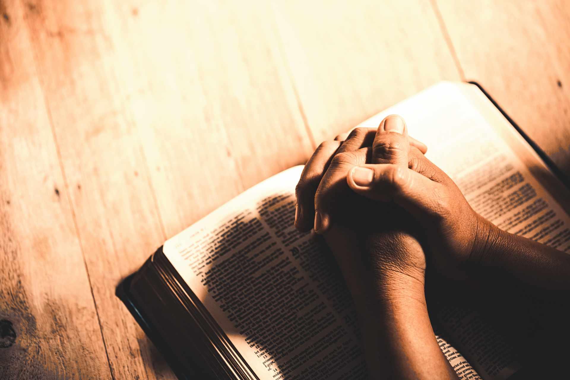 main jointe en prière sur la bible