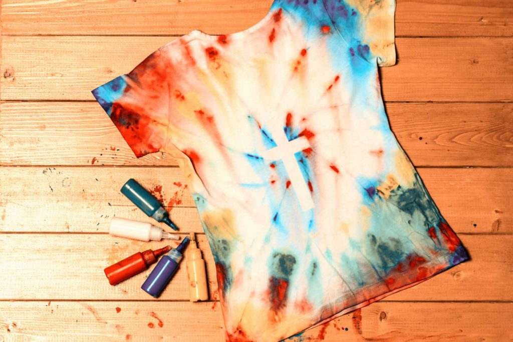 bricolage sur t-shirt fait avec des encres de couleurs spéciales avec au centre d t-shirt une croix blanche
